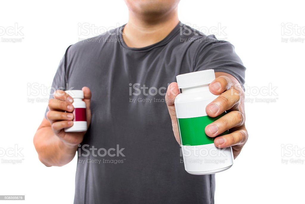 Man Comparing Brands of Dietary Supplements stock photo