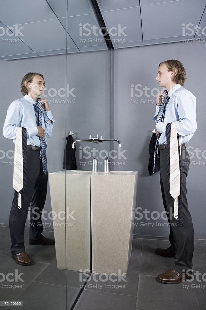 Man comparing ties in a mirror royalty-free stock photo