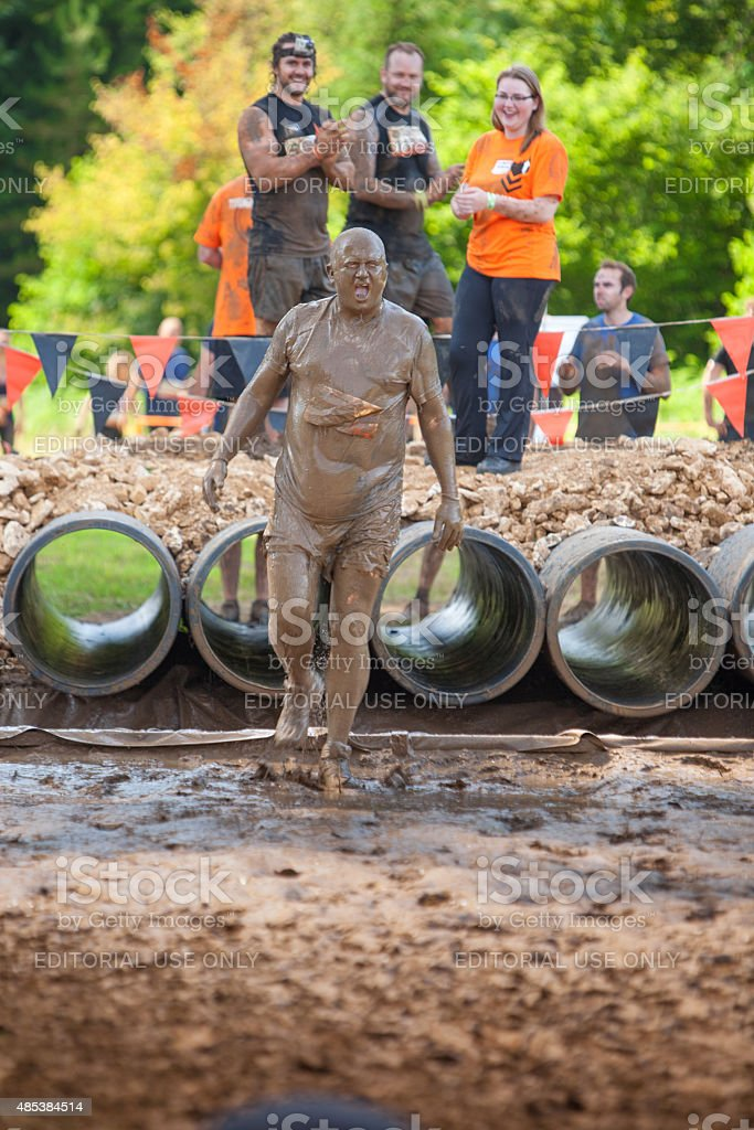 Man completely covered in watery mud stock photo
