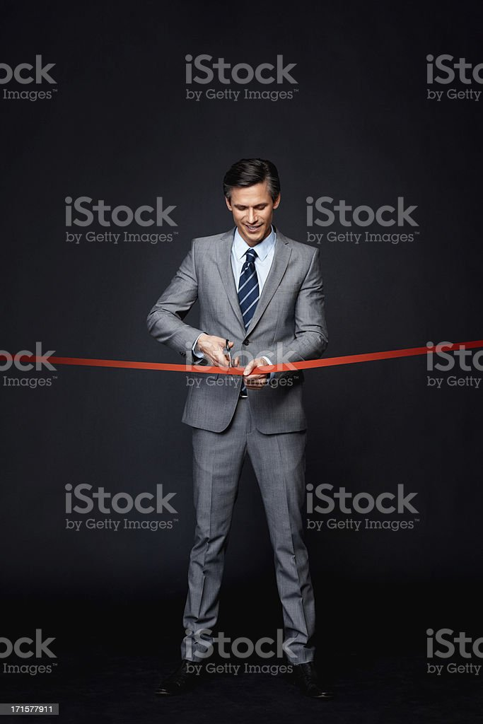Man concentrating while performing ribbon cutting ceremony stock photo