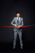 Man concentrating while performing ribbon cutting ceremony