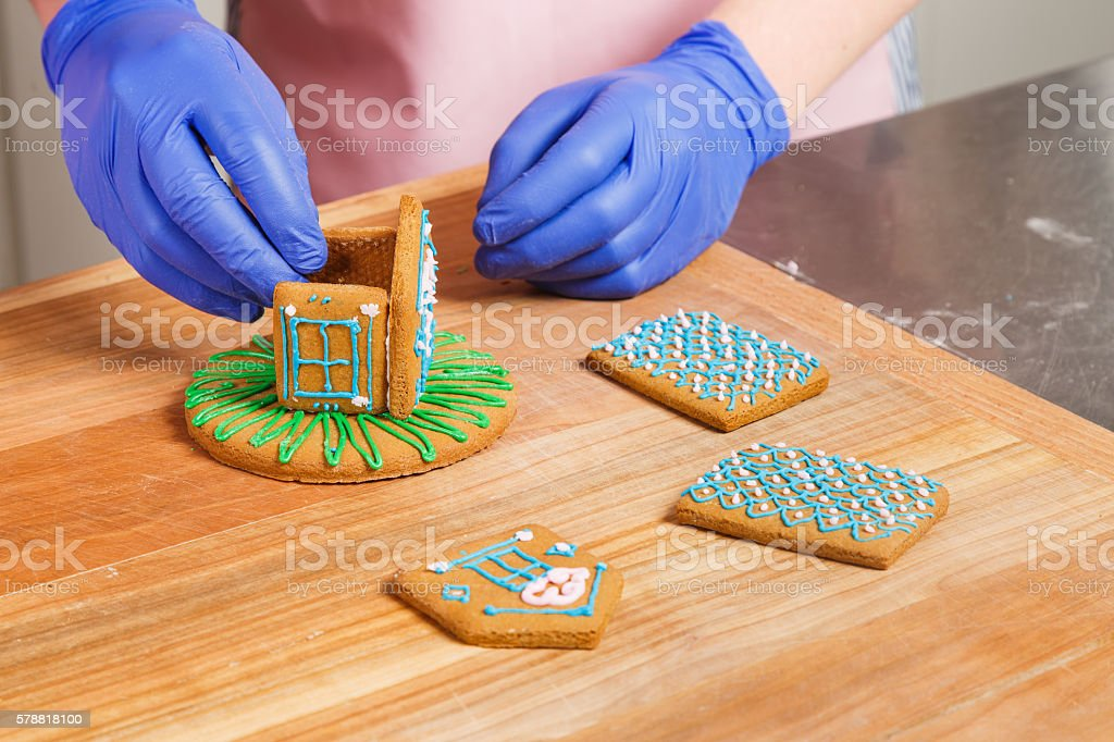 Man confectioner make a little house from gingerbread stock photo