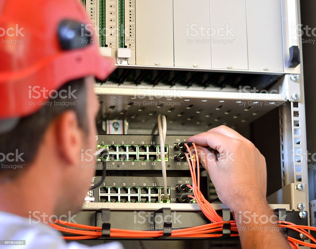 Man Connecting Fiber Optic Cable to the Switch stock photo