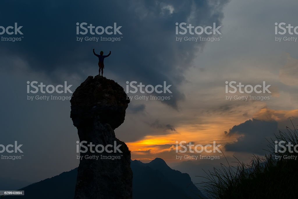 Man conquers the top of a mountain stock photo