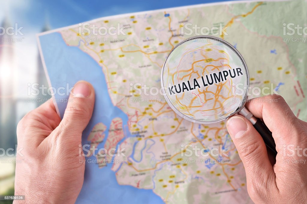Man consulting a map of Kuala Lumpur with magnifying glass stock photo