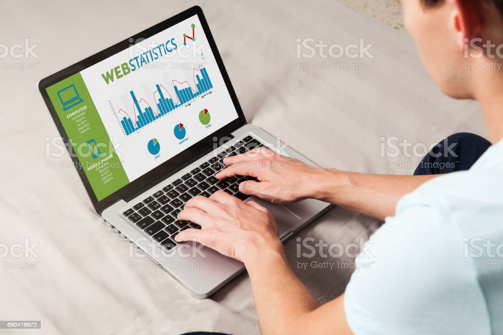 Man consulting web statistics in a laptop computer at home. stock photo