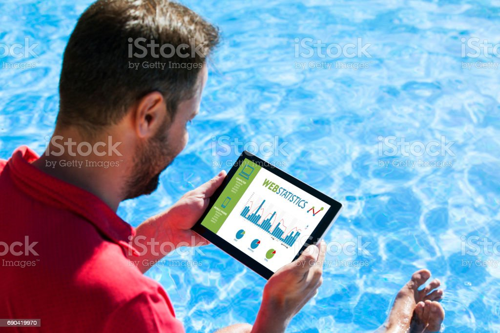 Man consulting web statistics with a tablet while sitting in the swimming pool edge. stock photo