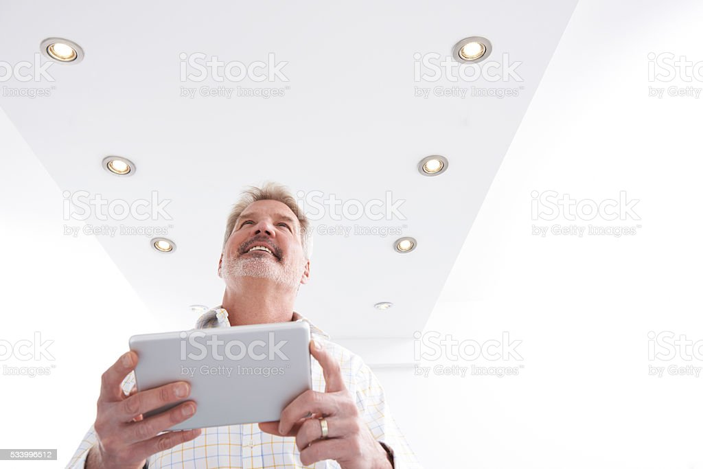 Man Controlling Lighting With App On Digital Tablet stock photo