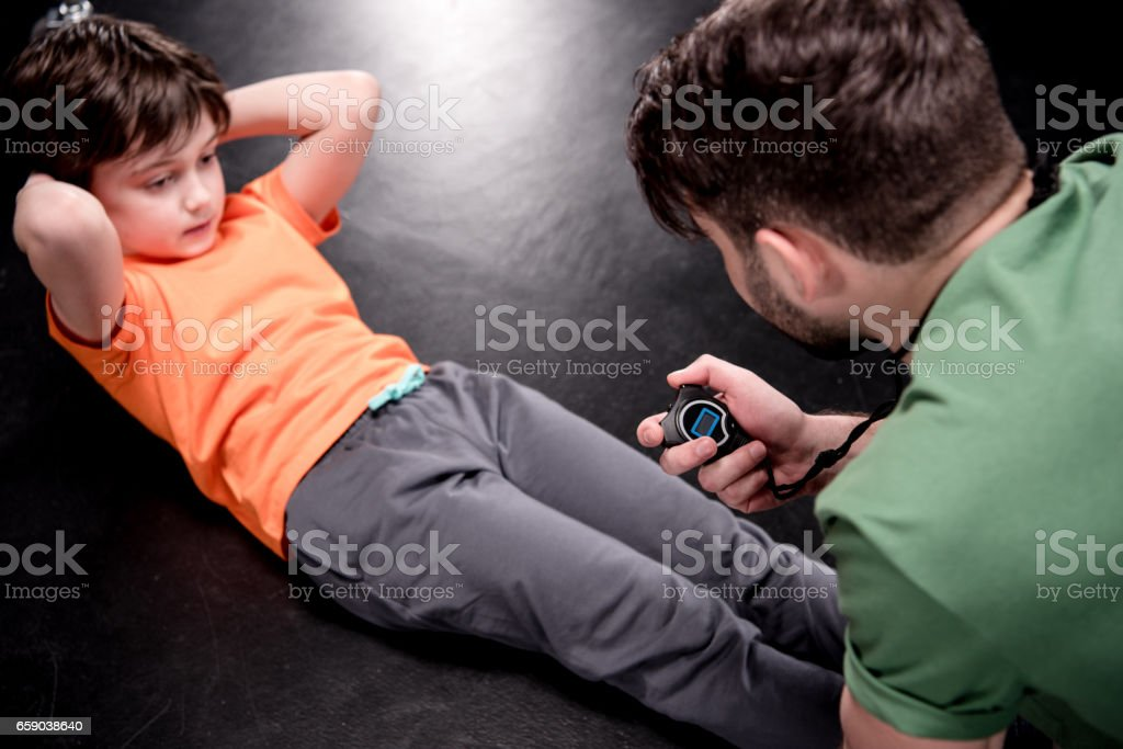 man controlling time while boy doing press exercise on black stock photo
