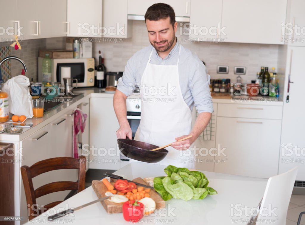Man cooking at home and preparing food stock photo