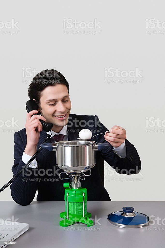 Man cooking egg at his desk stock photo