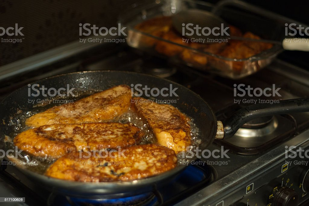 Man cooking French toast in the kitchen at home. stock photo