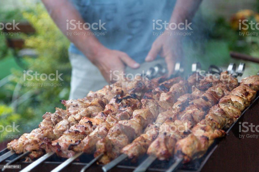 Man cooking kebab, meat grilling on metal skewer, close up stock photo