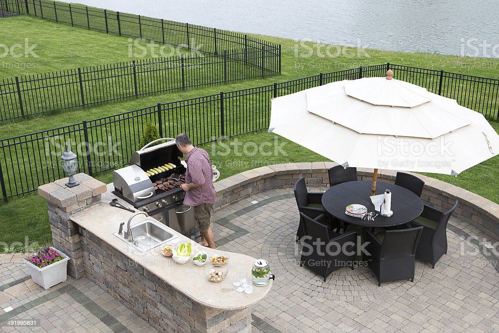 Man cooking meat on a gas BBQ stock photo
