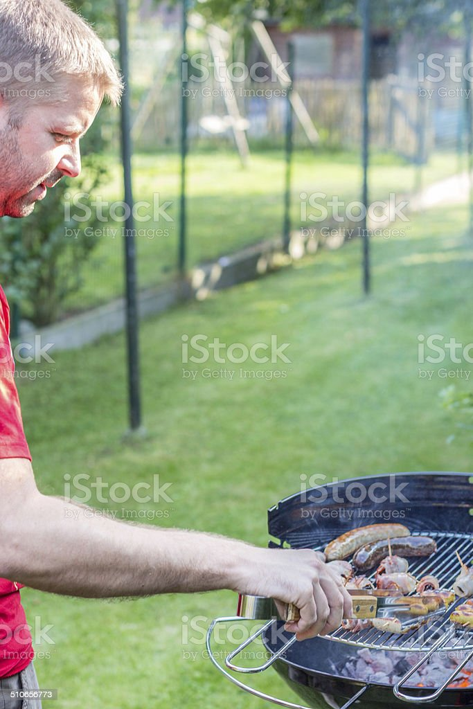 Man cooking meat on the barbecue stock photo