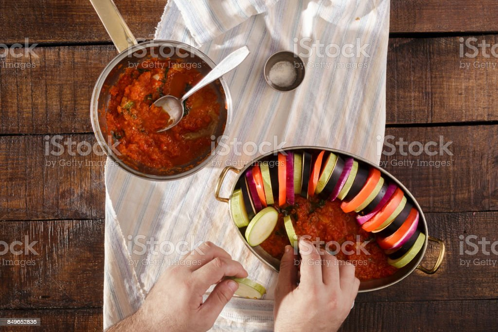 Man cooking ratatouille on a wooden table stock photo