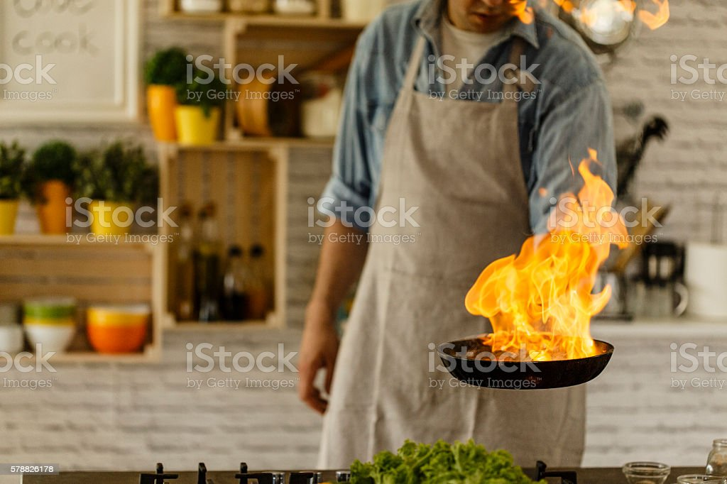 Man cooking with fire in kitchen stock photo