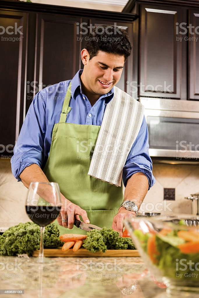 Man cooks dinner in home kitchen.  Salad, vegetables, wine. royalty-free stock photo