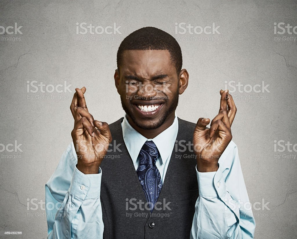 Man, corporate executive crossing his fingers, hoping for the best stock photo