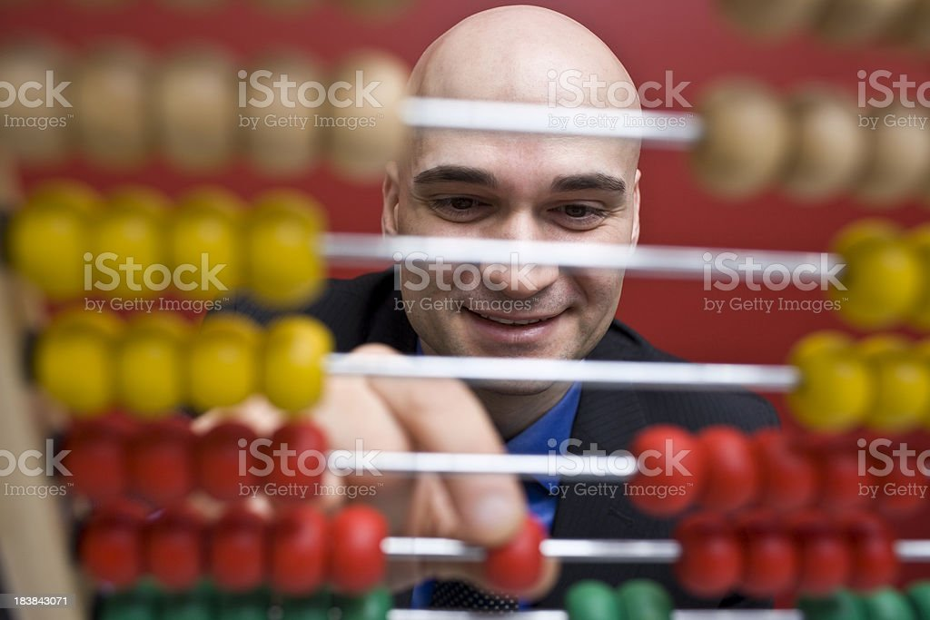 Man counting colorful beads on a Chinese calculator. royalty-free stock photo