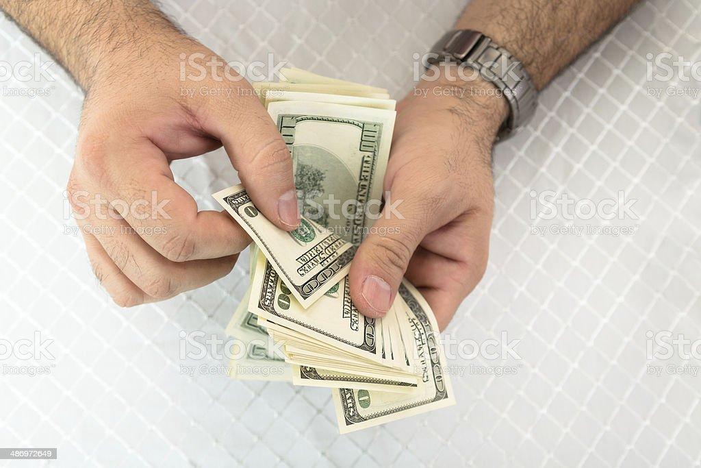 Man counting dollar notes stock photo