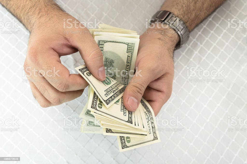 Man counting dollar notes stock photo