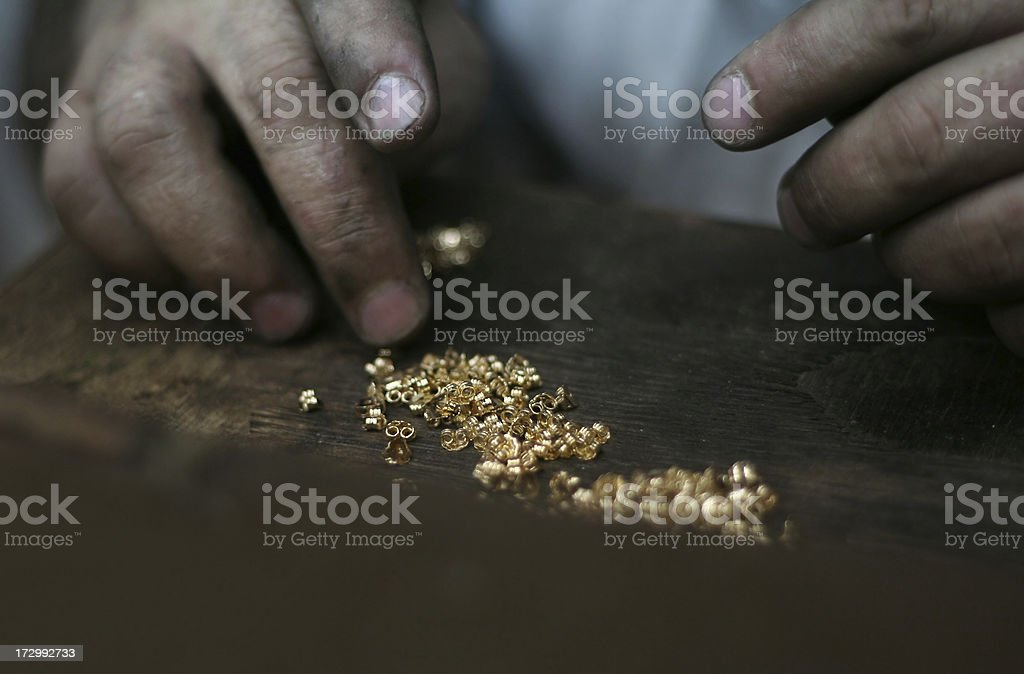 man counting gold nuggets stock photo