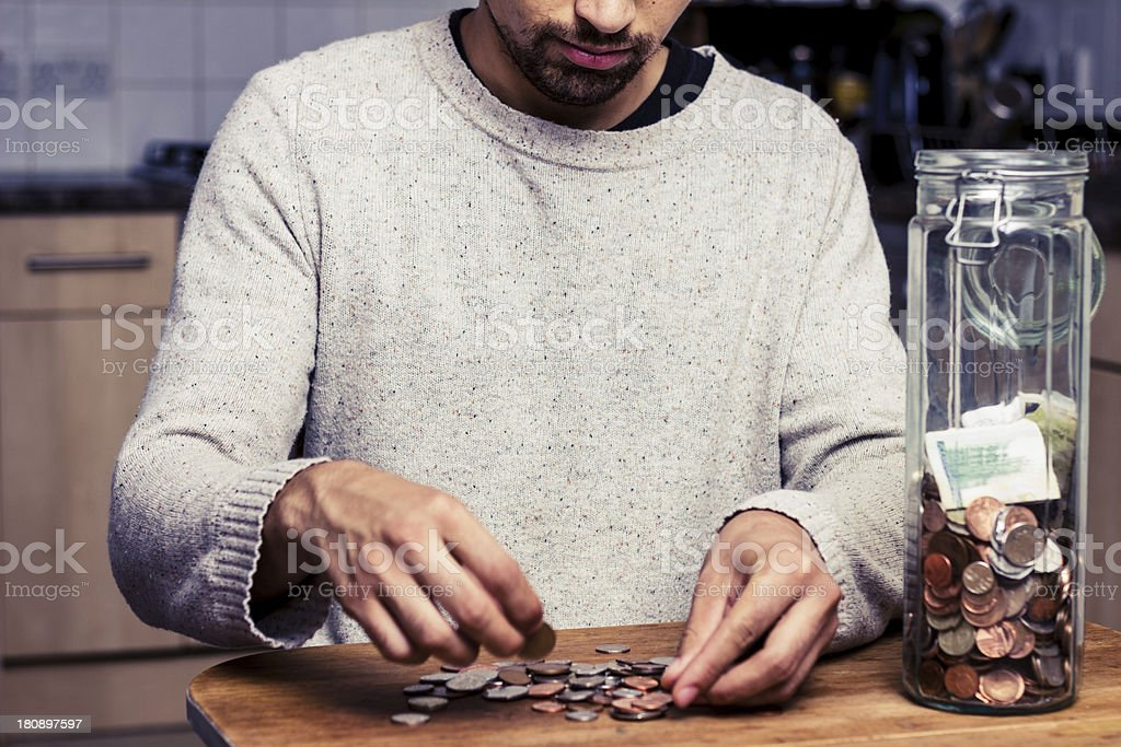 Man counting his money in kitchen royalty-free stock photo