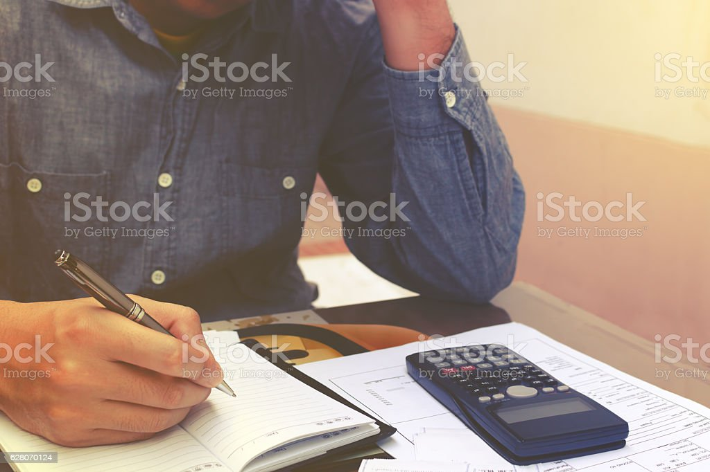Man counting using calculator and stress in problem with expenses.