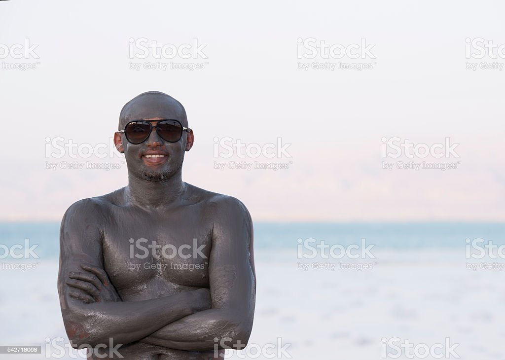 Man covered by mineral mud of Dead Sea. stock photo