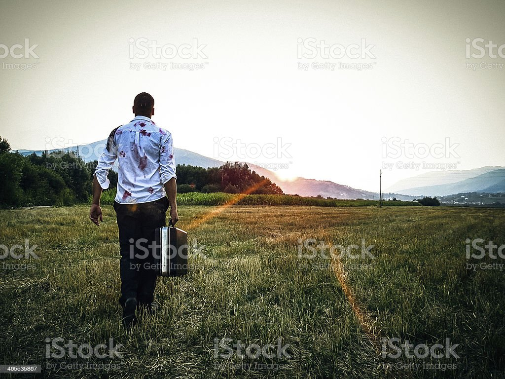Man covered in blood stains walking with a briefcase stock photo