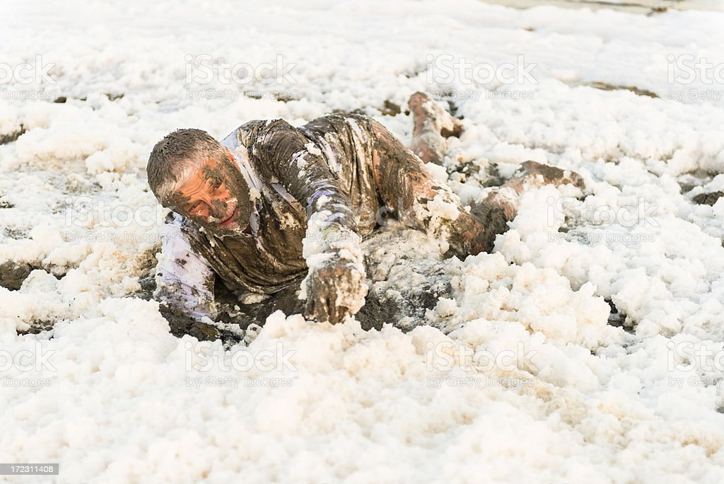 A man covered in mud crawling through foam asking for help. stock photo