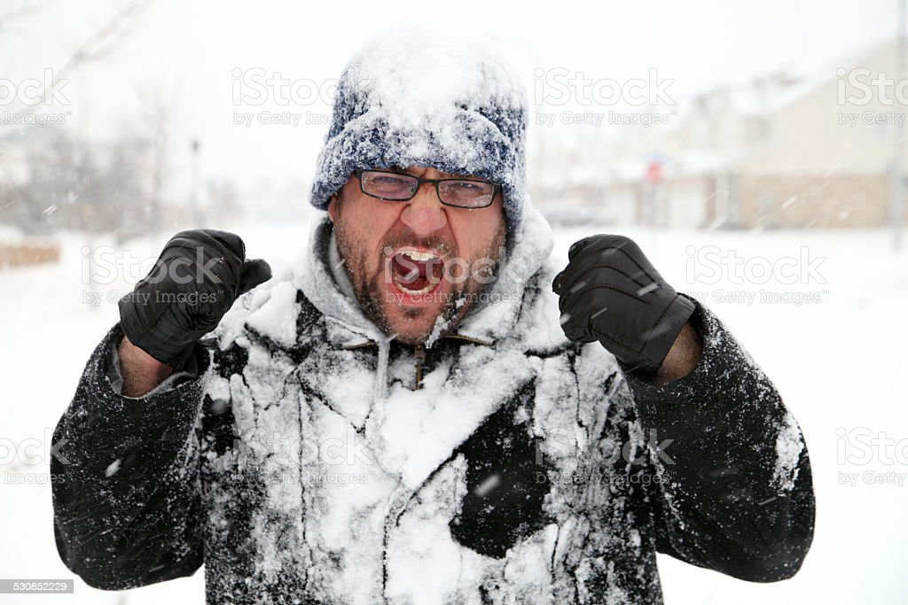 Man Covered In Snow Shakes Fists at Winter stock photo
