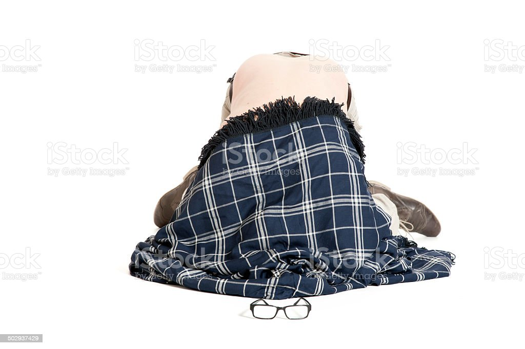 man covered with blanket on his knees on the floor stock photo