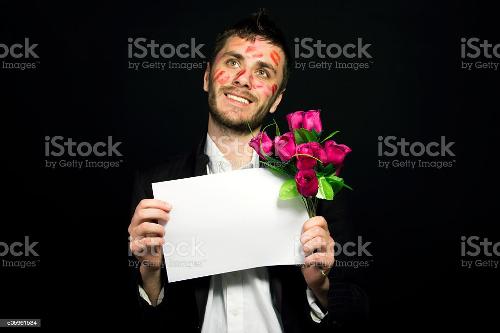 man covered with kisses holding roses stock photo