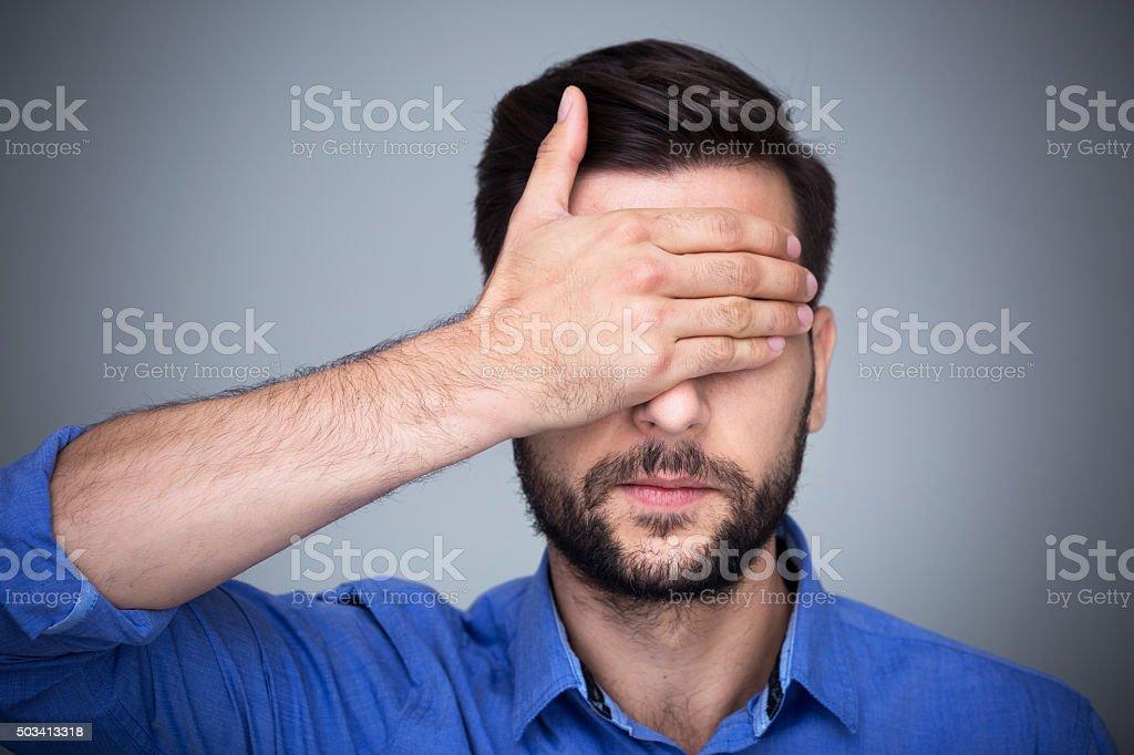 Man covering eyes stock photo