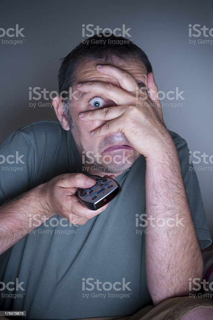 man covering face watching tv royalty-free stock photo