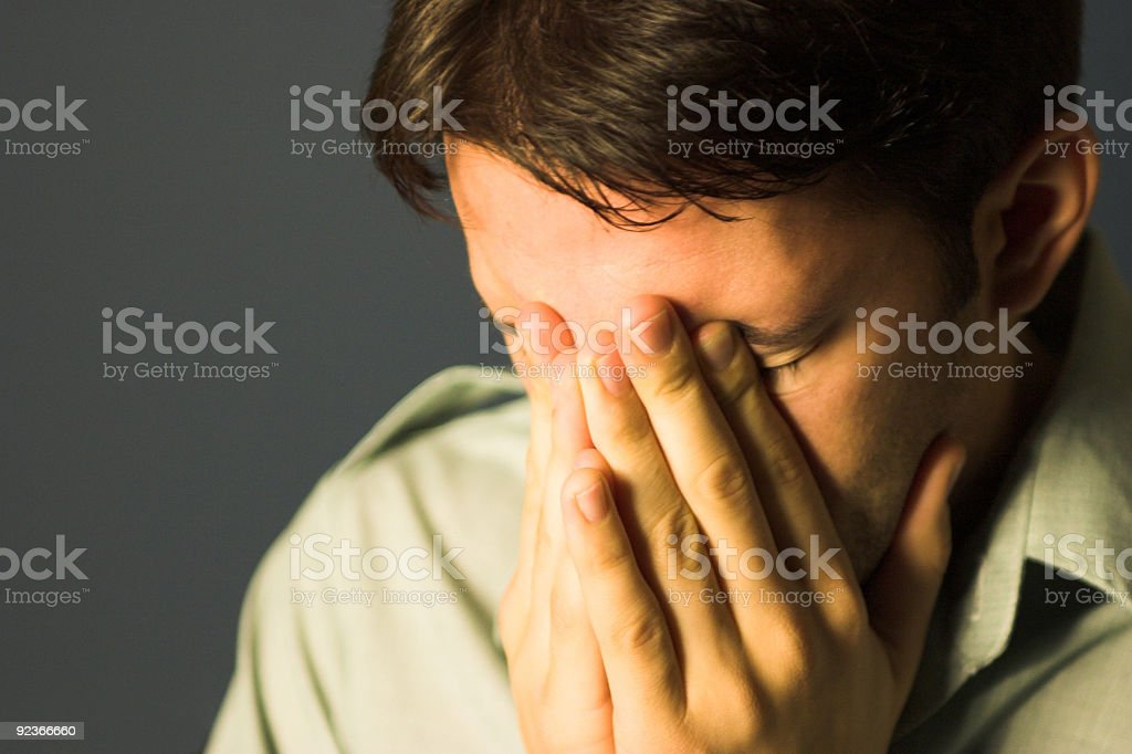 Man covering face with hands frustrated stock photo