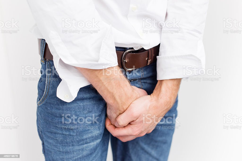 Man covering his crotch stock photo
