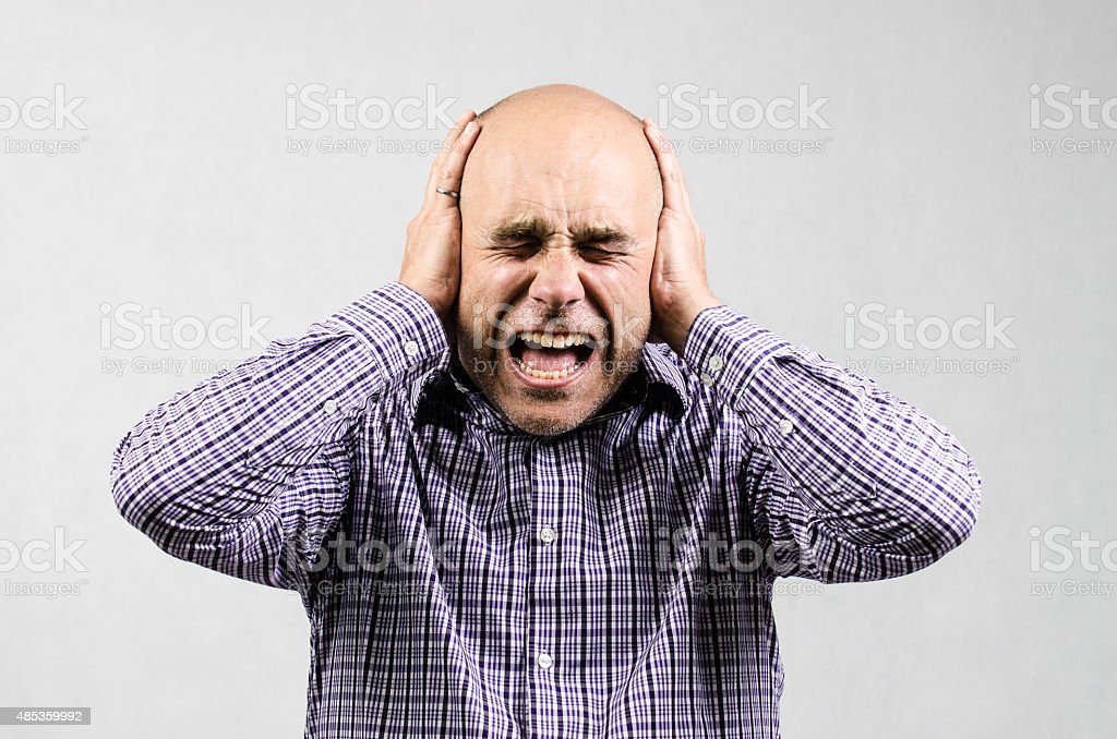 Man covering his ears and yelling stock photo