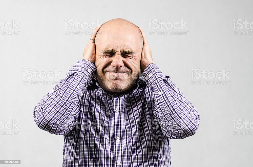 Man covering his ears stock photo