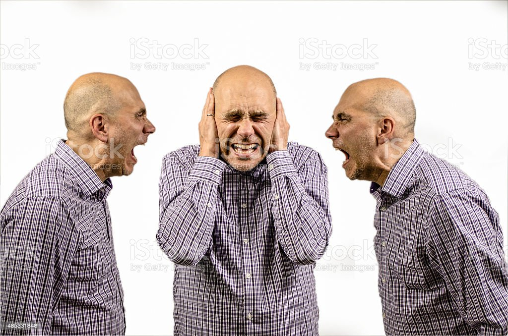 Man covering his ears while other shouting stock photo