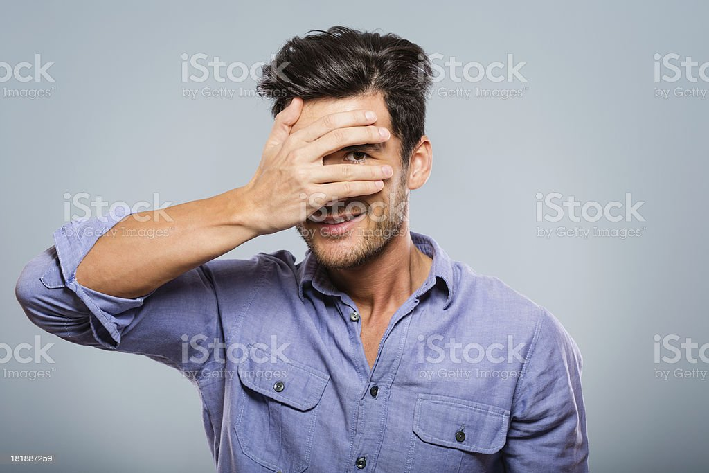 Man covering his eyes, peeking stock photo