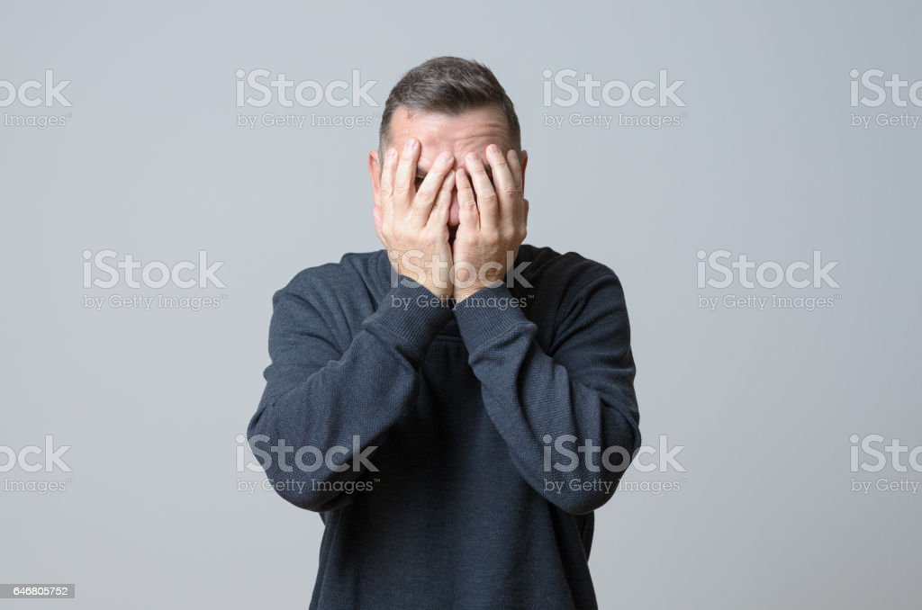 Man covering his face stock photo
