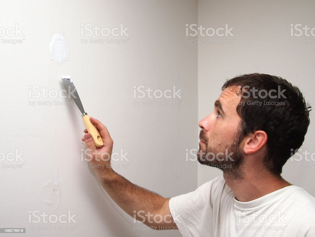 Man covering holes with a cement. stock photo