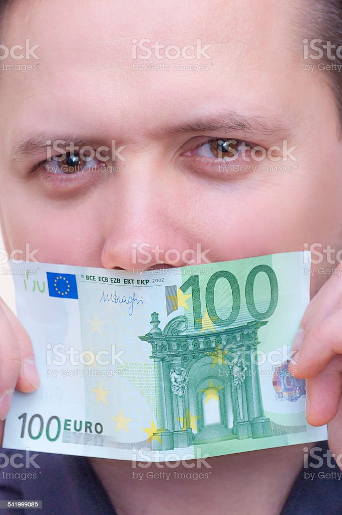 Man covering mouth with money, banknote, one hundred euro. stock photo