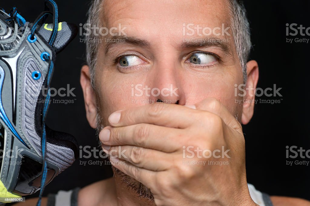 Man Covers Mouth After Smelling Shoe stock photo