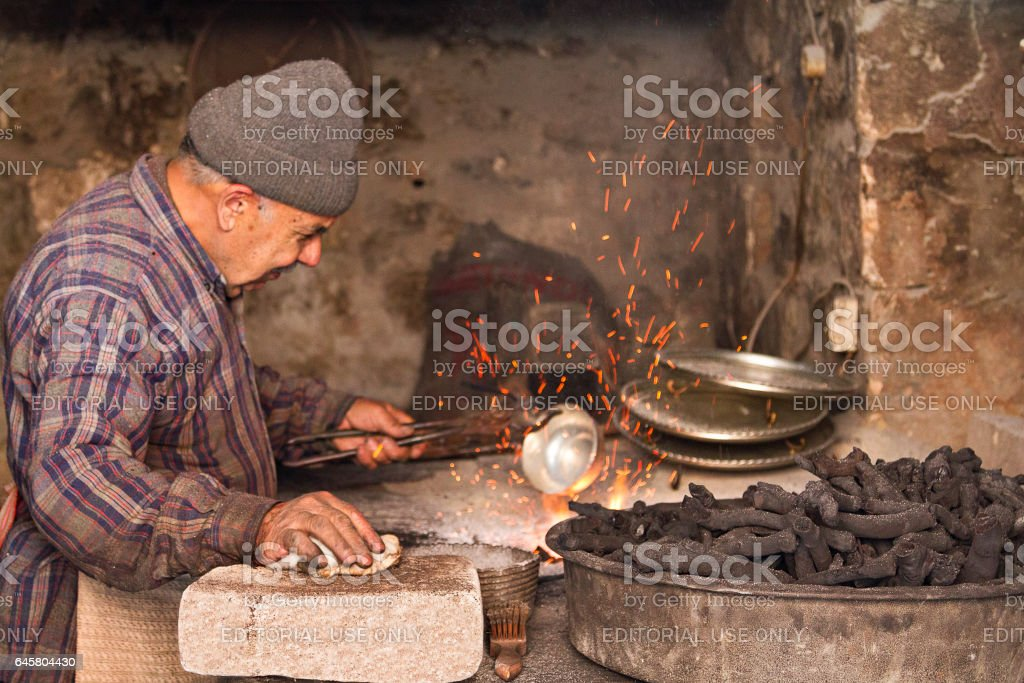 Mardin, Turkey - May 14, 2014: Man covers the copper bowl with tin, in Mardin, Turkey. He heats the copper so the tin would stick on it and wouldn't be poisonous. stock photo