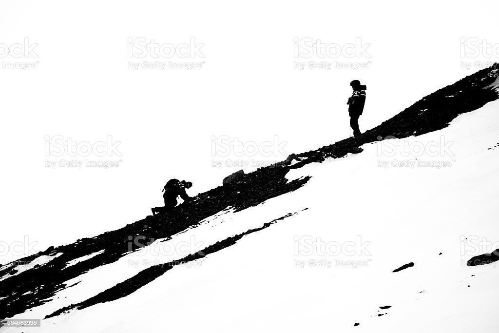 Man crawls towards man on rocky slope stock photo