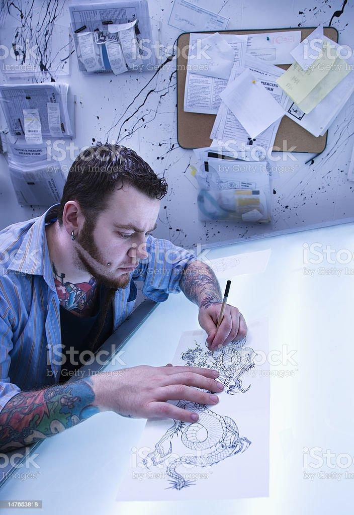 Man creating tattoo. stock photo